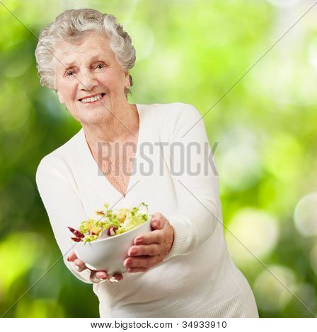 portrait of a senior woman showing a fresh salad against a nature background