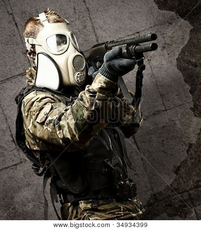 portrait of a young soldier with a gas mask aiming with a shotgun against a grunge wall