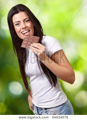 portrait of a young woman eating a chocolate bar against a nature background