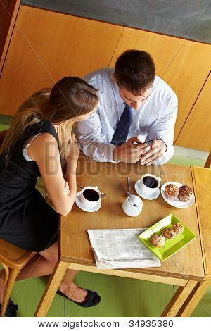 Two business people having a break in caf�© and looking at a smartphone