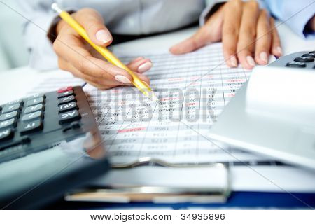 Photo of human hands holding pencil and marking numbers in documents