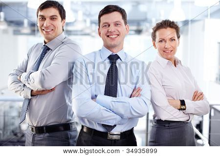 Elegant business team standing cross-armed expressing positivity and strong influence