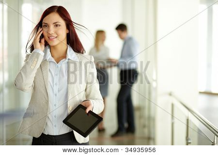 Business lady answering the phone with a smile with working team on background