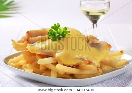 Grilled fish fillet in cheese batter and chips on a white plate