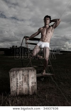 Dark evocative image of a muscular man balanced on portable steps posing in briefs outdoors under a stormy sky