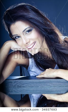 Toned portrait of a beautiful young brunette with a lovely smile leaning on a wooden beam with mirror image below
