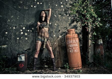 Gritty dramatic portrait of a sexy woman in skimpy shorts and boots posing against a grungy wall with a propane gas bottle at night