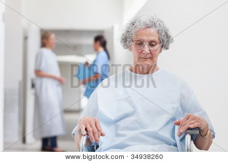 Elderly patient sitting in a wheelchair in hospital ward
