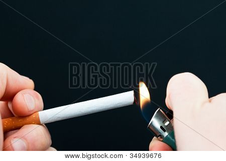 Someone lighting a cigarette against a white background