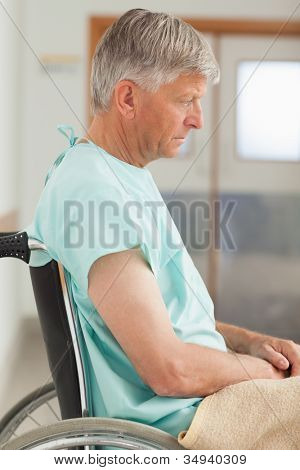 Sad man sitting in a wheelchair in hospital