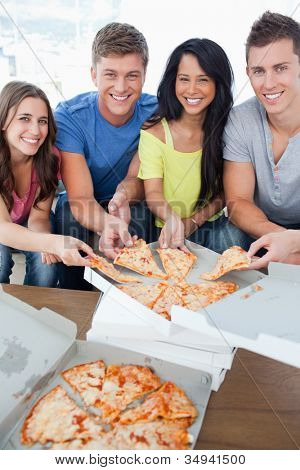 A smiling group of friends as they look into the camera and take some pizza