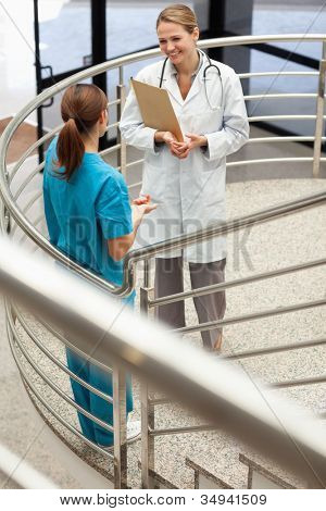 Doctor holding a file while talking to a nurse in a stairwell