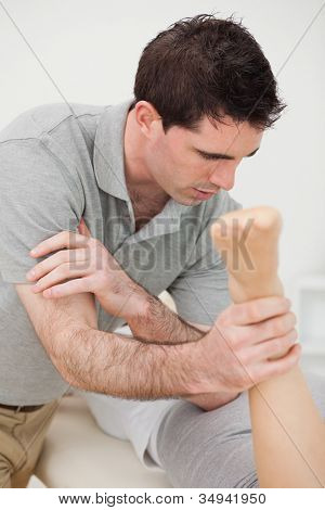 Doctor massaging a patient with his elbow in a room