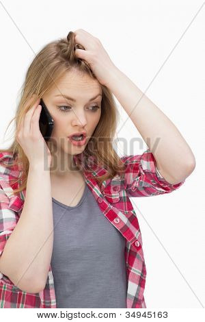 Annoyed woman holding a mobile phone against a white background