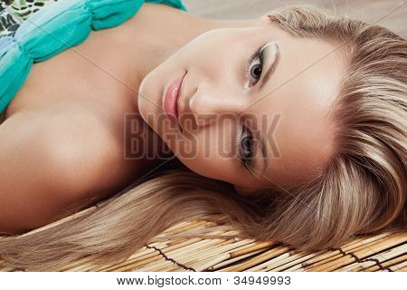 woman face laying on bamboo mat