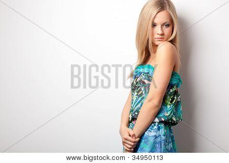 blonde woman posing near wall