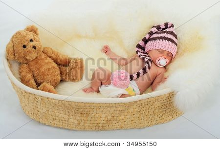 infant sleeping on a white sheepskin in a wicker basket.