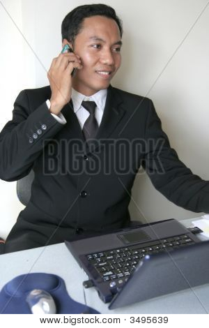 Asian Business Man Calling And Smiling In Office