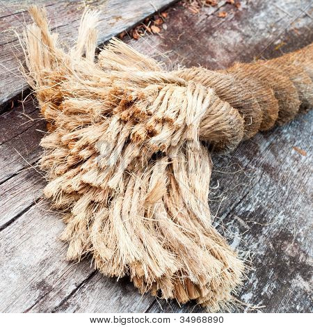 Frayed end of sisal rope lying on weathered wood