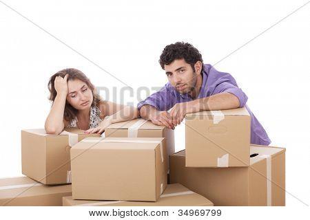 Casal jovem cansado com caixas de papelão, sobre fundo branco