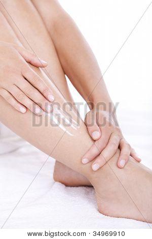 Woman applying moisturizer cream on the legs  over white background