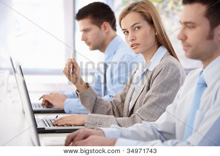 Young, attractive businesswoman sitting at meeting room, having business training.