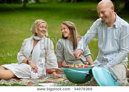 Two women talking while having a barbecue picnic in park