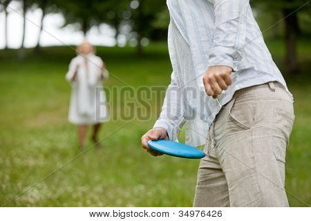 Midsection of man in casual wear ready to throw flying disc with woman in background
