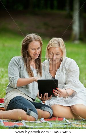 Caucasian mother and daughter using digital tablet while sitting comfortably on a picnic blanket