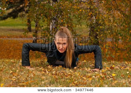 Beauty female doing push ups in the park