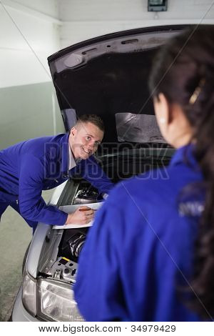 Mechanic leaning on a car while looking at a colleague in a garage