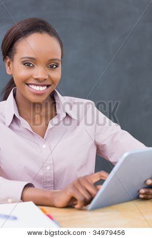 Teacher looking at camera while using a tablet computer in a classroom