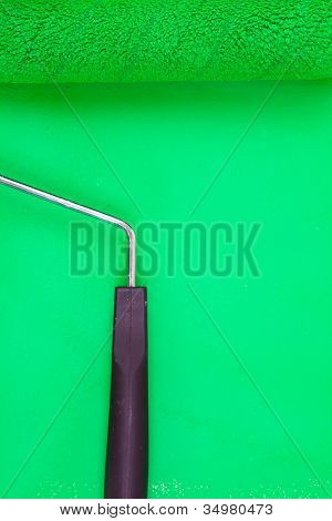 Green paint roller with handle on a background
