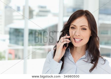 Young smiling manager talking seriously on the cell phone in front of the window