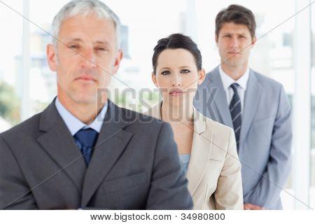 Jovem empresária séria acompanhada de seu empresário e um colega