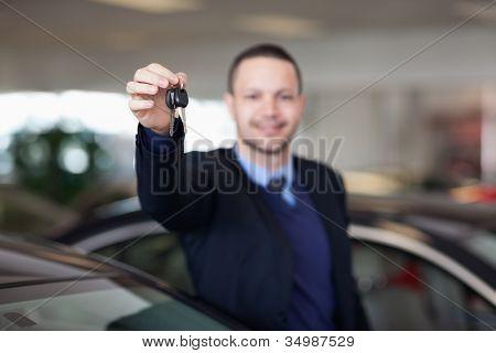 Dealer standing while holding car keys in a dealership