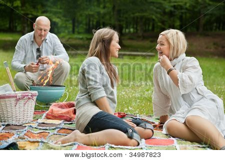 Friends visiting and preparing a barbecue for outdoor picnic