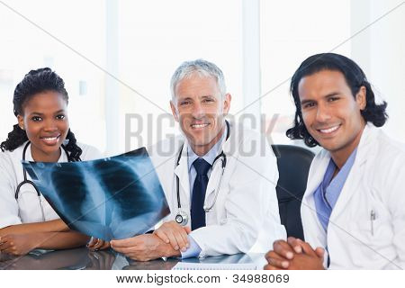 Confident medical team smiling while working hard with a patient's x-ray