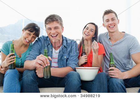 A laughing group of friends enjoying some beers and popcorn together