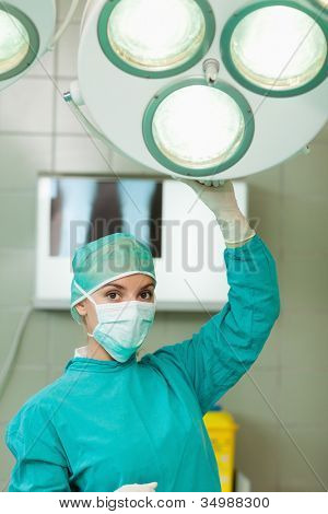 Surgeon holding a surgery light in a surgical room
