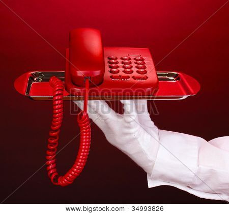 Hand in glove holding silver tray with telephone on red background
