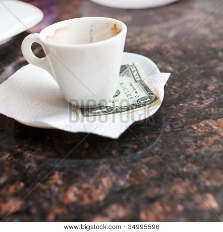 dollar bills under a coffee cup