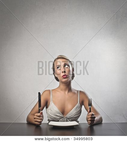 Young woman sitting in front of a dish at lunchtime