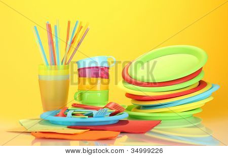bright plastic disposable tableware on colorful background