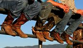 stock photo of wrangler  - Well worn boots adorn the wranglers at rodeo in small county fair Idaho - JPG