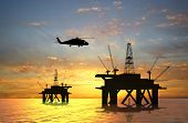 foto of oil rig  - Oil rig silhouette over orange sky  - JPG