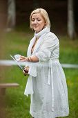 Beautiful mature woman in casual wear playing badminton in park on a weekend outing