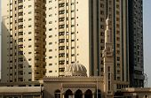 image of urbanisation  - Little mosque in front of tall high - JPG