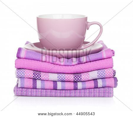 Coffee cup over kitchen towels. Isolated on white background