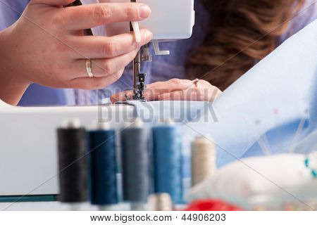 woman's hands using sewing machine with reels of colour threads and other sewing accessories like pins, buttons and thimble